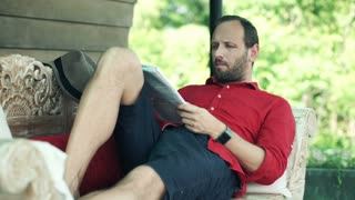 Young man reading magazine, relaxing on wooden sofa on terrace