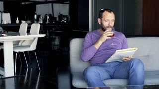 Young man reading newspaper and drinking red wine sitting on sofa at home