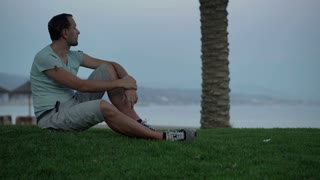 Young man relaxing on the grass close to the beach
