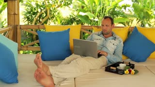 young man finish his work on laptop and relaxing with coffee on gazebo bed in garden