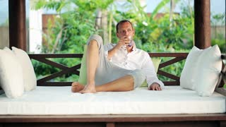 young man relaxing with drink on gazebo bed in garden