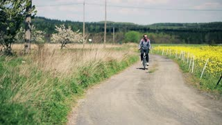 Young man ride bike on the country road