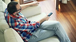 Young man sitting at sofa and watching tv