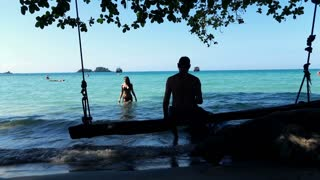 Young, man sitting on the swing looking at beautiful woman walking out the sea, slow motion shot at 120fps
