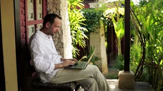 young man sitting with laptop on bench in front of country house