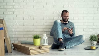 Young man sitting with smartphone on floor at his new home