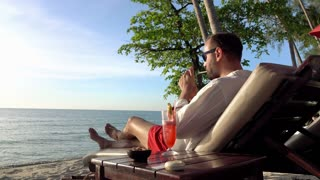 Young man smoking cigarette and drinking cocktail on sunbed close to the sea, 4K