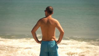 Young man standing on the beach, super slow motion
