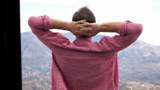 Young man stretching arms while standing on terrace with mountains view, 240fps