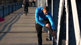 Young man stretching legs, woman jogging across the bridge in city, super slow motion, 120fps