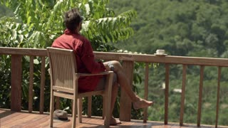 Young man sunbathing at relaxing while sitting on terrace with jungle view