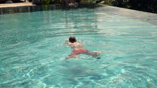 Young man swimming in pool, super slow motion 240fps