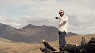 Young man taking photo of splendid mountains view