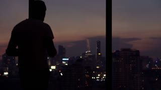 Young man taking photo of the modern city standing on the window at home