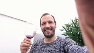 Young man taking selfie photo while standing with wine on terrace