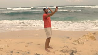 Young man taking selfie with his cellphone o the beach, super slow motion