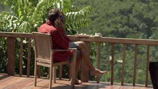Young man talking on cellphone and cooling himself while sitting on terrace with jungle view