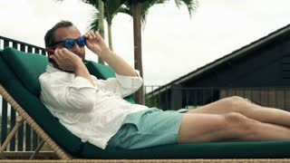 Young man talking on cellphone lying on sunbed on terrace
