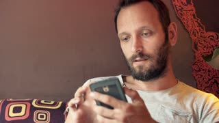 Young man texting on smartphone in cafe