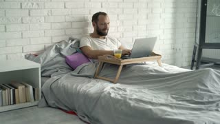 Young man using laptop lying on bed, 4K