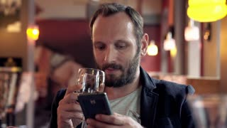 Young man using smartphone and drinking red wine in cafe