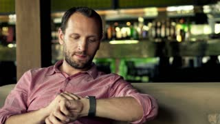 Young man using smartwatch while sitting in cafe