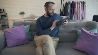 Young man using tablet computer while sitting on sofa at home, 4K