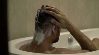 Young man washing body in bathtub, 4K