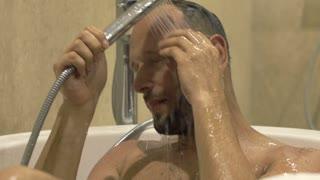 Young man washing body in bathtub