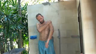 Young man washing his arms standing under shower in the garden, super slow motion