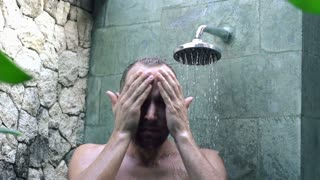 Young man washing his face under shower super slow motion 240 fps