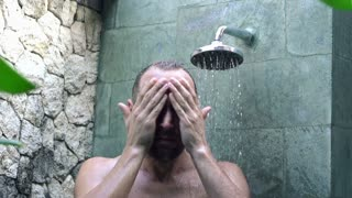 Young man washing his face under shower