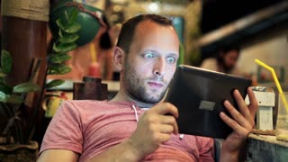 Young man watching film on tablet computer in trendy cafe