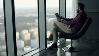 Young man watching movie on tablet computer sitting on chair by window with city view