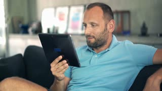 Young man watching movie on tablet computer sitting on sofa at home. 4K