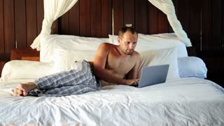 Young man with laptop relaxing on comfortable bed