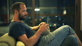 Young man with smartphone sit on sofa in home at night