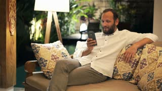 Young man with smartphone sitting on sofa in home at night