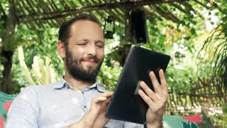 Young man with tablet computer in the garden