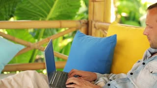 young man working with laptop on gazebo bed in garden
