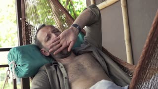 Young man yawning and wake up after a nap on hammock on terrace, super slow motion, shot at 240fps