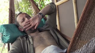 Young man yawning and wake up after a nap on hammock on terrace