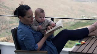 Young mother trying read book while sitting on the terrace with her little son