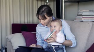 Young mother working with tablet while her son playing with smartphone on sofa at home