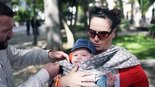 Young parents wearing baby sling in the city park