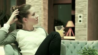 Young pensive woman drinking and relax on chair at home