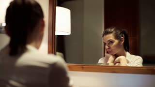 Young pensive woman looking at her reflection in the mirror