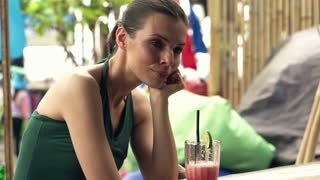 Young, pensive woman mixing cocktail sitting in bar close to the beach, super slow motion, shot at 240fps