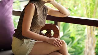 Young, pensive woman sitting on the beautiful terrace