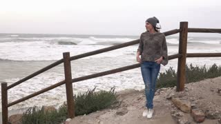 Young pensive woman standing on the beach, 240fps